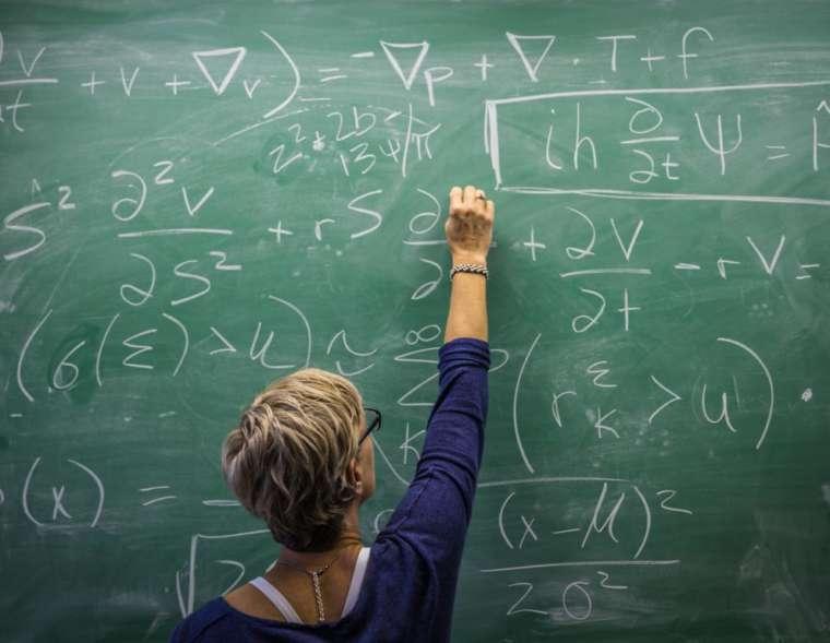 Lehrerin schreibt an eine Tafel