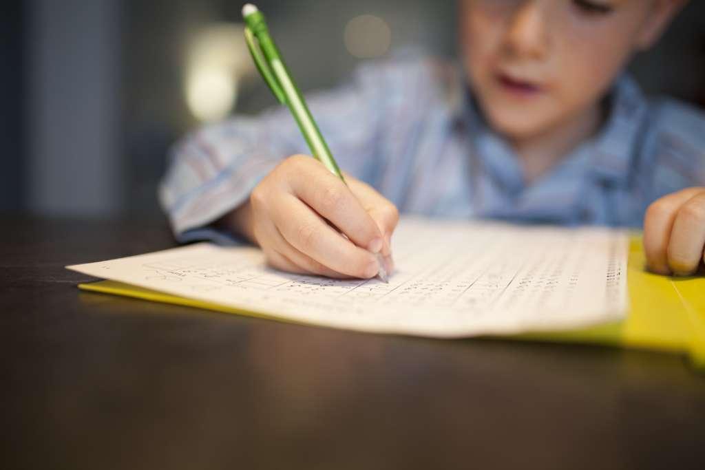 Ein Junge löst Hausaufgaben und schreibt die Lösungen in ein Heft.