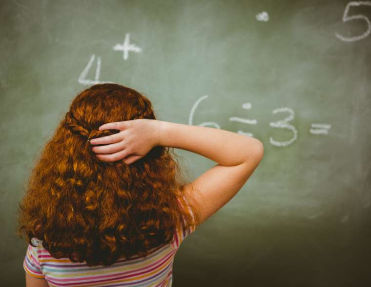 Rückenansicht einer jungen Schülerin vor einer Tafel. Sie kratzt sich am Kopf.