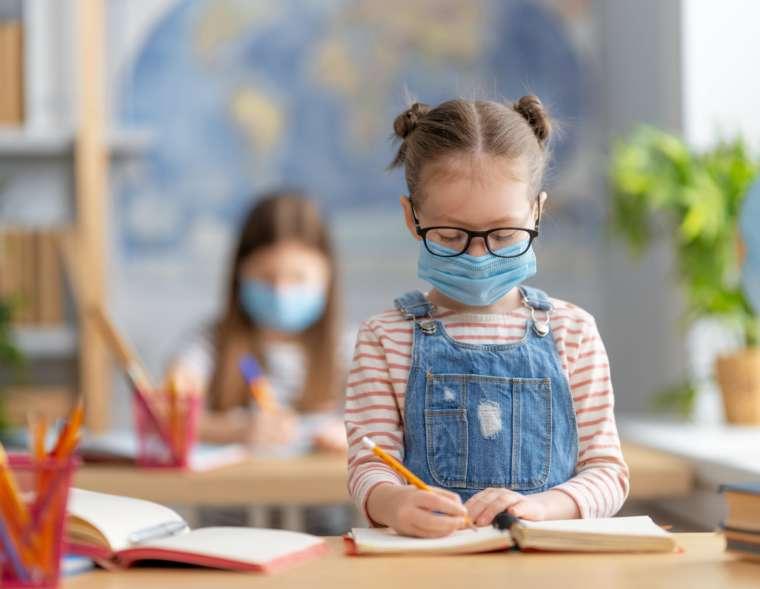 Zwei Mädchen sitzen mit Maske im Klassenraum und lernen.