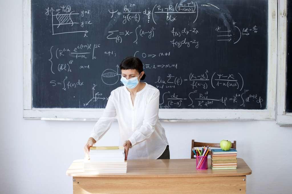 Lehrerin mit Maske vor einer Tafel.