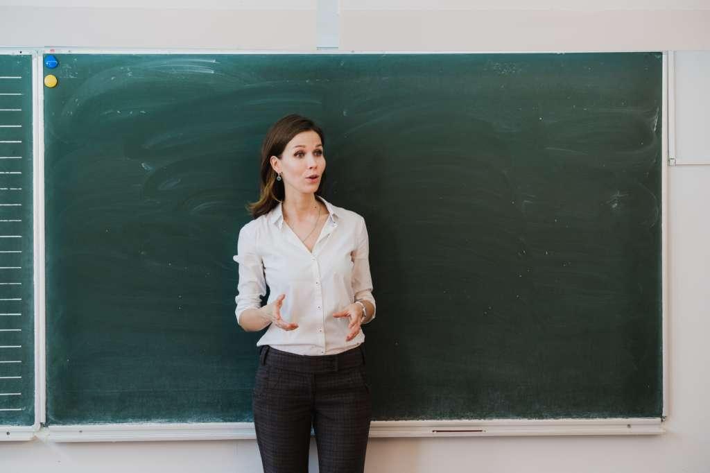 Lehrerin steht gestikulierend vor einer Tafel.